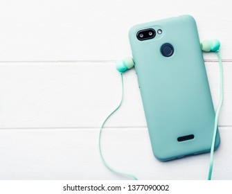 Azure digital telephone with body protection and blue headphones at the white table, close-up with space for pattern