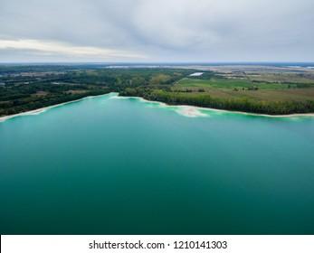 "Azure lake ""Osadnik Gajowka"" top view, abstract fantasy green and brown pattern background"