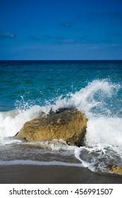 Azure sea with rock and sea foam