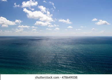 Azure sea water under blue cloudy sky. Aerial view. Horizon at center.