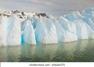 Azure shimmering beautiful iceberg in Antarctica with green reflection. Green color from underneath around icebergs is rarely seen.