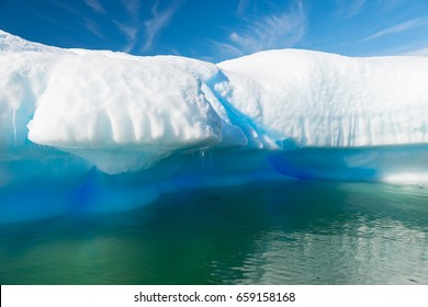 Azure shimmering beautiful iceberg in Antarctica with green reflection.