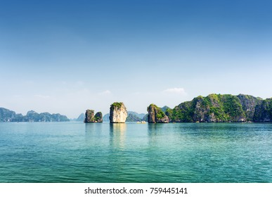 Azure water of the Ha Long Bay at the Gulf of Tonkin, the South China Sea, Vietnam. View of lagoon and karst towers-isles on blue sky background. The Halong Bay is a popular tourist destination.