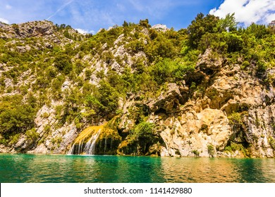 The azure waters of the river flow between the steep walls of Limestone Canyon Verdon. Adorable little waterfall on the wall of the gorge. Concept of ecological and active tourism