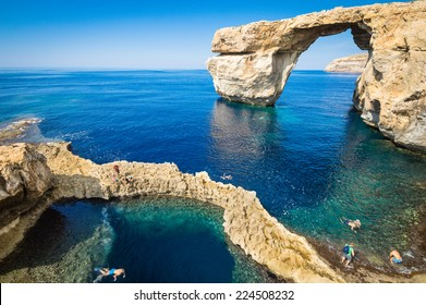 The Azure Window in Gozo island - Mediterranean nature wonder in beautiful Malta - Unrecognizable touristic scuba divers - World famous rock formation landmark collapsed after sea storm