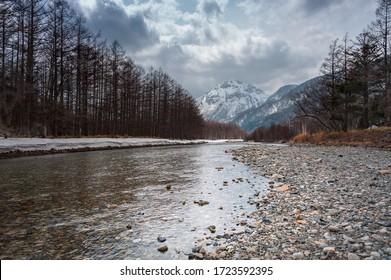 Azusa River and Hotaka Mountains, Kamikochi, Nagano, Japan. Winter landscape, tranquil scene with moody, cloud sky