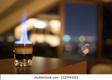 B-52 on a Mission, flaming cocktail shot on a counter-top with a bokeh background.