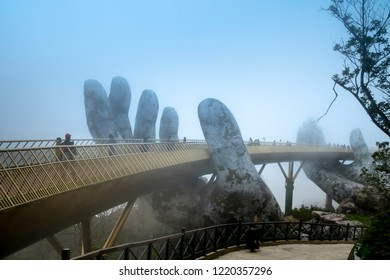 Ba Na Hill mountain resort, Danang city, Vietnam - October 19, 2018: The Golden Bridge is lifted by two giant hands in the tourist resort on Ba Na Hill in a foggy day at Danang, Vietnam.