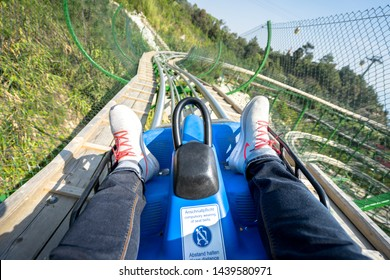 Ba Na Hill / Vietnam - March 2019 : A tourist is playing hill-side roller coaster at Ba Na Hill. This is signature playing thing in Vietnam. The rail will go down along the view of mountain valley.