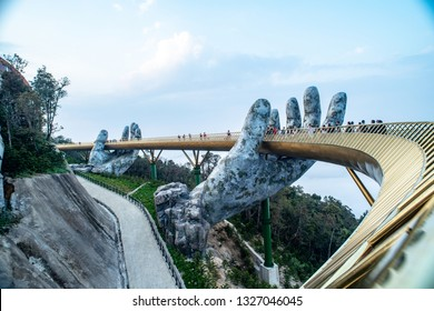 "Ba Na Hills. Da Nang, Vietnam - February 26 2019:  Tourists in Golden Bridge known as ""Hands of God"", a pedestrian footpath lifted by two giant hands"