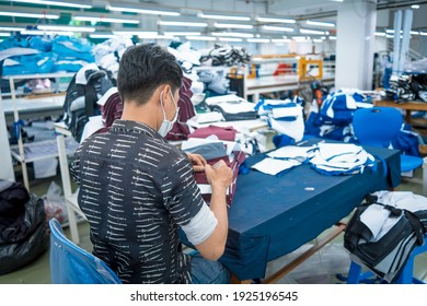 Ba Ria, VIETNAM - 26 FEB 2021: Man wearing medical mask writting number on fabric after finished cut. Textile cloth factory working process tailoring workers equipment