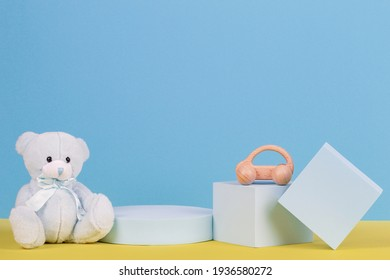 Babby kid toys background. Teddy bear, wooden car and geometric shapes podium, platforms on light blue and yellow background