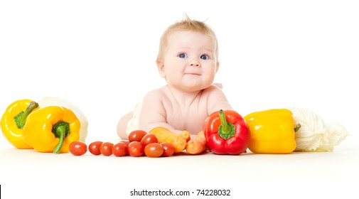 The babe in an environment of the fresh vegetables, isolated on the white
