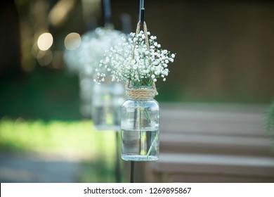 Babies Breath floral arrangement in mason jars at wedding ceremony isle