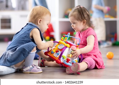 Babies conflict in nursery. Child girl trying to take away toy from another kid.