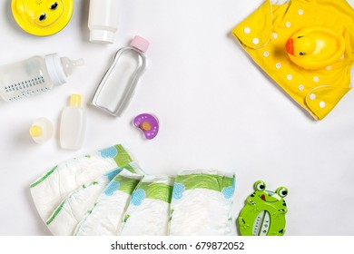 Babies goods diaper, baby powder, cream, shampoo, oil on white background with copy space. Top view or flat lay.