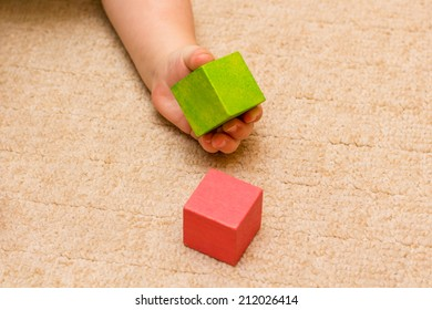 Babies hands playing with colored blocks