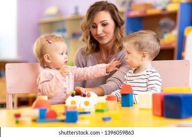 Babies with mentor in kindergarten. Kids toddlers in nursery school. Little girl and boy preschoolers playing with teacher.