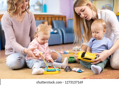 Babies play and their mothers communicate in playroom in daycare