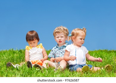 Babies sit on grass against blue sky