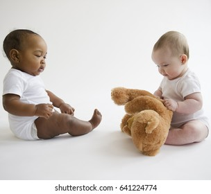 Babies sitting together on floor with teddy bear
