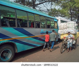 Babughat interstate bus terminal, Kolkata, 01-09-2021: A van-rickshaw driver carrying heavy weight luggage in his cart, to be transported by bus. Few luxury buses are seen parked at roadside.