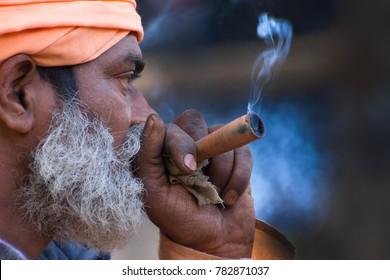 BABUGHAT, KOLKATA, WEST BENGAL / INDIA - 10TH JANUARY 2015 : Hindu Sadhu smoking marijuana, locally called Ganja, a form of canabis sativa .