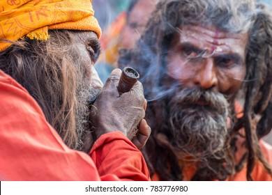 BABUGHAT, KOLKATA, WEST BENGAL / INDIA - 10TH JANUARY 2015 : Hindu Sadhu smoking marijuana while another Sadhu looking at him, locally called Ganja, a form of canabis sativa .