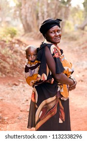 BABUNGO KINGDOM - CAMEROON / 01.19.2015: African mother carrying her baby on her back