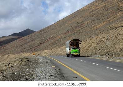 Babusar Pass, Khyber Pakhtunkhwa, Pakistan - October 7, 2016: A green truck climbs the Karakoram Highway between Gilgit Baltistan and Khyberpakhtunkhwa province at an altitude of 4,200 meters.