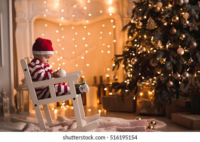 Baby 1 year old wearing santa claus suit sitting in rocking chair with Christmas tree and lights on background in room. Merry Christmas. Holiday season.