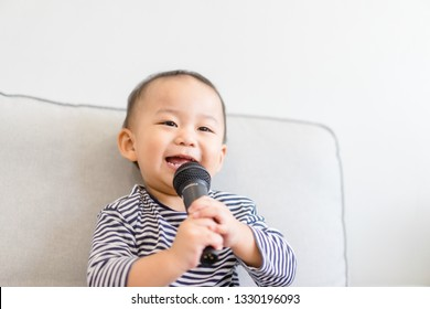 Baby 2 years old boy holding microphone and singing at home.Baby boy relax learn to sing in music song class.Family with children and Art Education for Child.