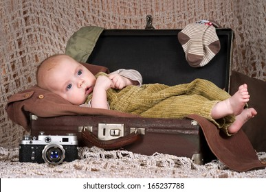 Baby (3,5 months) lies in the retro-suitcase
