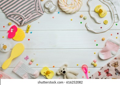 Baby accessories background: baby jumpsuit, socks, soother and toys over white wooden background with copy space; top view, flat lay