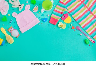 Baby accessories background: baby jumpsuit, socks, soother and toys over green background with copy space; top view, flat lay