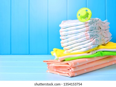 Baby accessories background. Pile of diapers, napkins and dummy.