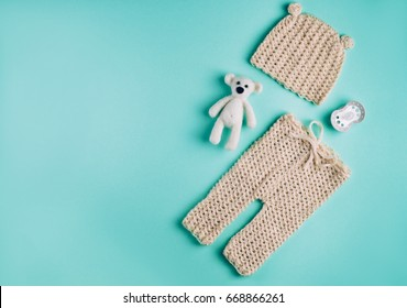 Baby accessories background: small hat and pants for newborn baby, dummy and bear toy over light green background with copy space; top view, flat lay