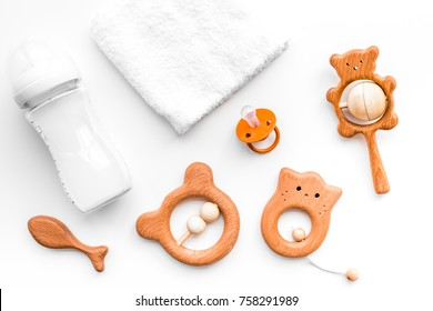 Baby accessories. Wooden toys, pacifier and bottle on white background top view