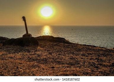 A baby acoustic guitar,leaning against rocks near the edge of the cliffs,near Gokarna beach,about to be played as the sun sets