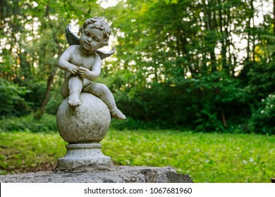 Baby angel or cupid figure made of stone in green summer garden.