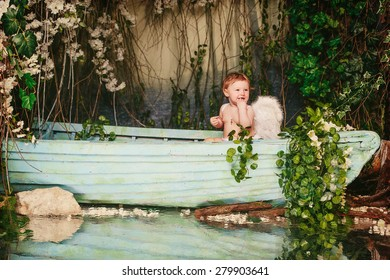 Baby with angel wings in a boat with flowers  background