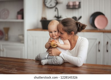 Baby with an apple and caring mother in the kitchen in a real interior. The concept of a healthy childhood, mom's love and the first lure.