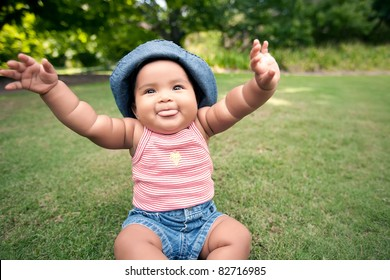 baby with arms in the air and blowing raspberries