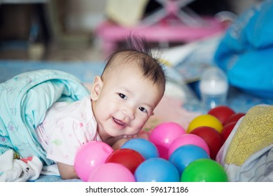 Baby Asian girl playing colourful ball in the room.