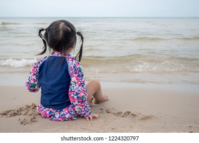 Baby Asian girl sit at front of beach, concept for relaxing, vacation with copy space.