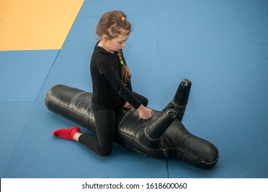 Baby attacks a punching bag in the form of a man. A little girl sits on top on a training mannequin and works off punches. The child beats the training dummy with his hands