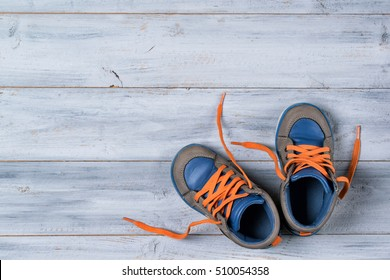 Baby Autumn shoes on wooden background, top view