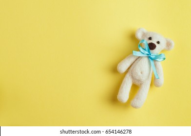 Baby background: bear toy with turquoise bow-knot over yellow background with copy space; top view, flat lay