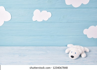 Baby background with white teddy bear and clouds on blue wooden table