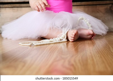 Baby ballerina feet on a wooden floor in white tutu